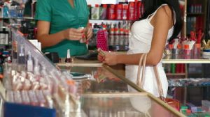 stock-footage-woman-paying-for-beauty-care-products-at-the-cash-counter